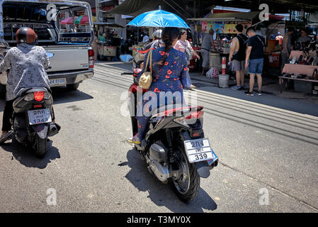 Woman riding motorcycle and holding an umbrella as a sun shade. Thailand Southeast Asia - Stock Image