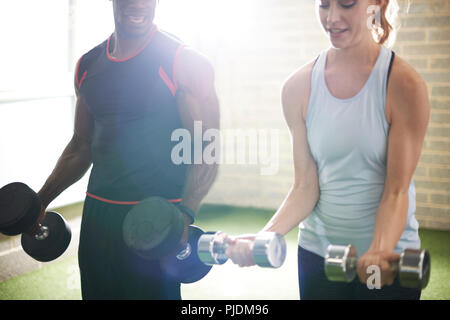 Trainer and female client lifting dumbbells in gym - Stock Image