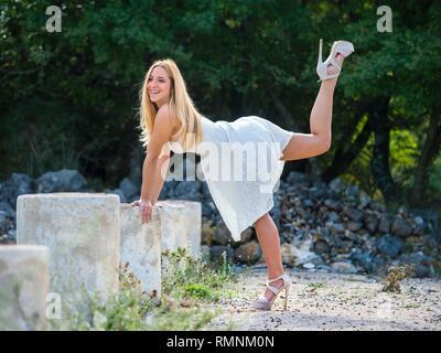 Pretty teen girl smiling balancing standing on one leg legs heels giggle giggling - Stock Image