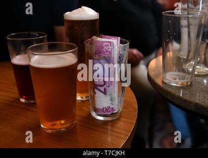 A pint glass full of money known as a kitty which is a set contribution of money for each member present to pay for drinks - Stock Image