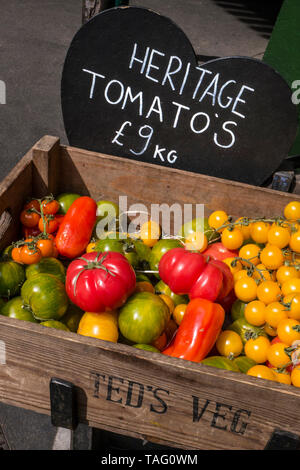 Heritage Tomatoes Teds Veg home grown display at Borough Market with heart shaped blackboard price tag An heirloom tomato (also called heritage tomato in the UK) is an open-pollinated (non-hybrid) heirloom cultivar of tomato. According to tomato experts, heirloom tomatoes can be classified into four categories: family heirlooms, commercial heirlooms, mystery heirlooms, and created heirlooms. They usually have a shorter shelf life and less disease resistance than hybrids bred to resist against specific diseases. They are grown for a variety of reasons, for food, historical interest & taste - Stock Image