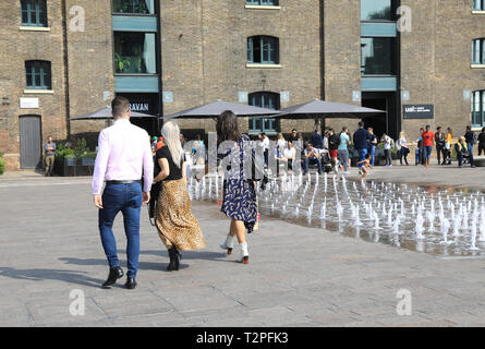 Caravan Kings Cross on Granary Square, from across the fountains in the spring sunshine, in north London, UK - Stock Image