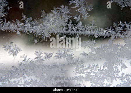 Ice crystals forming on a cold window in winter creating a natural, crystaline work of art - Stock Image