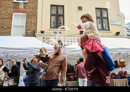 Children and adults parents playing with bubbles having fun on a London street fair fayre UK Britain - Stock Image