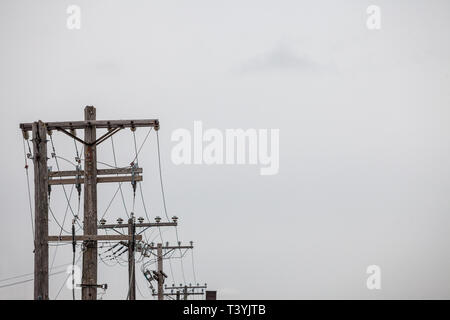Electric and telephone power line, old and outdated, on a rotten wooden pole, abiding by North American standards, in the city of Ottawa, Ontario, Can - Stock Image