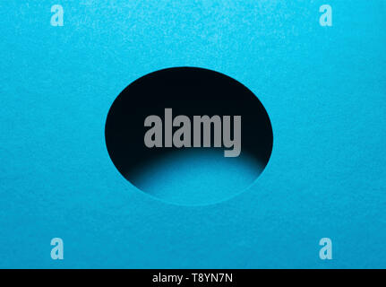circular shaped hole with shadow on blue cardboard paper - Stock Image