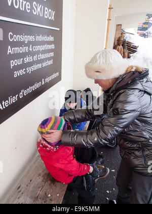 mother and small children wearing winter clothes getting changed after skiing - Stock Image