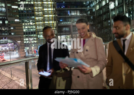 Business people reviewing paperwork on urban pedestrian bridge at night - Stock Image