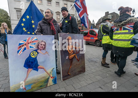 London, UK. 15th January 2019. Political artist Kaya Mar holds his paintingsof May and Corbyn. Groups against leaving the EU, including SODEM, Movement for Justice and In Limbo and Brexiteers Leave Means Leave and others protest opposite Parliament as Theresa May's Brexit deal was being debated.  While the two groups mainly kept apart, a small group, some in yellow jackets came to shout insults at pro-EU campaigners, while police tried to keep the two groups separate. Credit: Peter Marshall/Alamy Live News - Stock Image