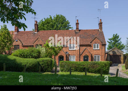 Terrace of old brick built cottages overlooking the village green, Great Brington, Northamptonshire, UK - Stock Image