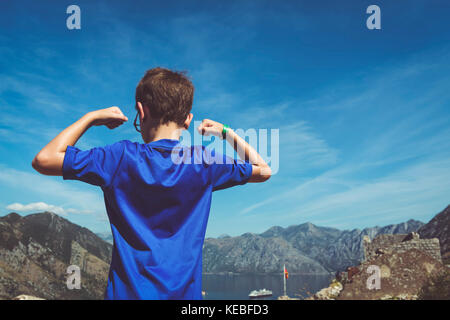The view from the fort above Kotor after a long climb with a boy in the foreground showing his muscles - Stock Image
