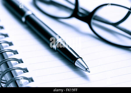 Pen and prescription glasses on lined spiral notebook paper toned blue - Stock Image
