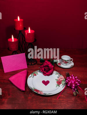 Floral pattern china dinnerware with matching plate, cup and saucer. pink rose, pink napkin, silverware, red candles and pink card - Stock Image