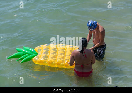 Bournemouth, UK. 7th July 2018. Playing with inflatables in the sea in Bournemouth during the July heatwave. Credit: Thomas Faull / Alamy Live News - Stock Image