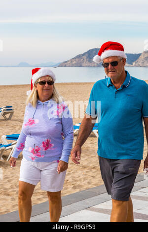 Benidorm, Costa Blanca, Spain, 25th December 2018. British tourists dress for the occasion on Christmas Day in this favourite getaway destination for Brits escaping the cold weather at home. Temperatures will be in the mid to high 20's Celsius today in this mediterranean hotspot. Middle aged couple wearing Christmas Jumpers walking outside on the sea front promenade on Levante Beach. - Stock Image