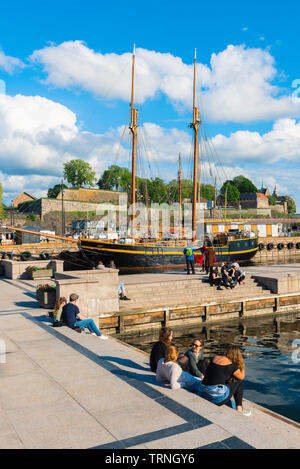 Oslo harbor, view of young people relaxing beside a quay in the harbor area (Aker Brygge) in Oslo on a summer afternoon, Norway. - Stock Image