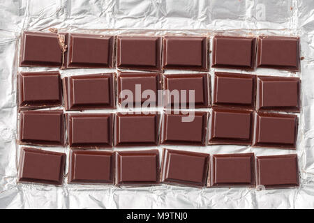 Crushed into pieces of a dark chocolate bar in the metal foil packaging. - Stock Image