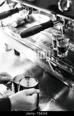 making espresso coffee BW black and white close up detail with modern cafe machine and glasses - Stock Image