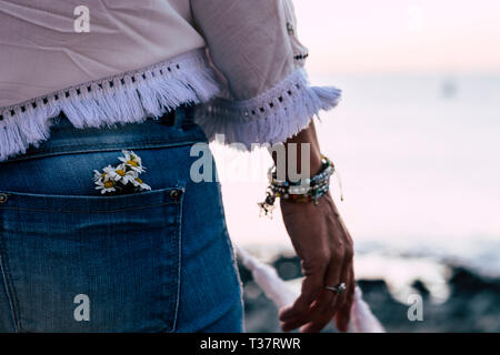 Nature environment concept with group of daisies flower inside a back pocket of jeans - style and fashion closeup of rear woman - defocused background - Stock Image