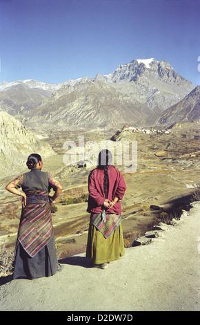 Two Tibetan style ladies view Jharkot village from path to Kagbeni on Annapurna circuit Nepal Himalayas Purkung - Stock Image