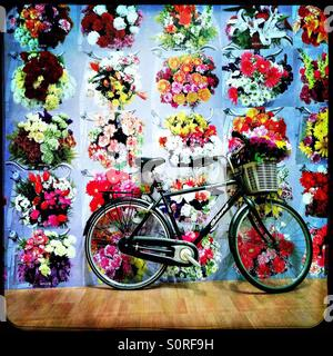 Bicycle with floral wallpaper art installation - Stock Image
