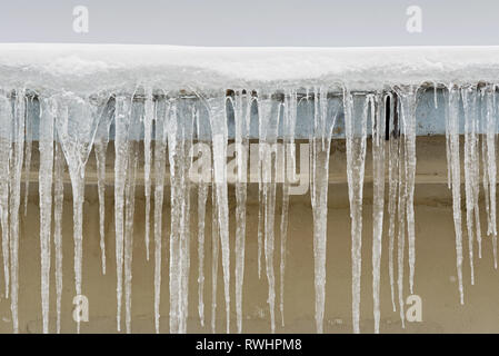 Big icicles hang from the roof of a house - Stock Image