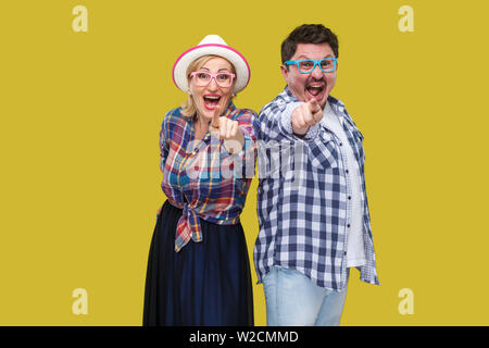 Couple of friends, adult man and woman in casual checkered shirt standing together back to back pointing finger, looking amazed, surprised or laughing - Stock Image