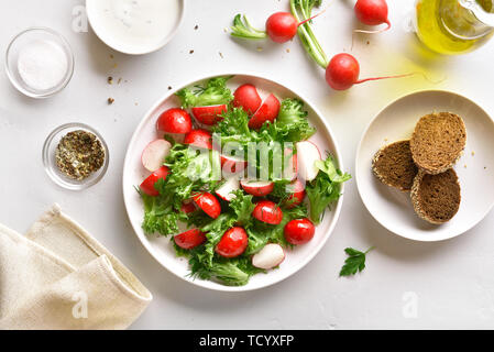 Radish salad with lettuce leaves on plate over white stone background. Top view, flat lay - Stock Image