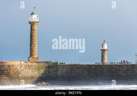 Whitby, Yorkshire, UK. 11th February, 2019. U.K. Weather. Whitby, North Yorkshire, England. 11th February 2019. Visitors to the North Yorkshire coast at Whitby enjoying a bright but cold walk along the seashore with the old lighthouse and harbour in the background. Alan Beastall/ /Alamy Live News - Stock Image