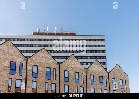 New built houses along Evans Street in Southampton in contrast with an old building in brutalist style architecture, Southampton, England, UK - Stock Image
