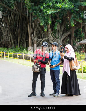 Young Malaysians Taking a Photo, KLCC Park, Kuala Lumpur, Malaysia. - Stock Image