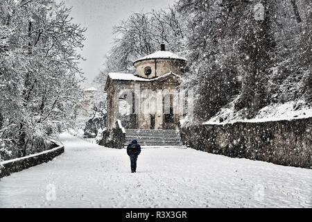 solitary man walking under the snow on the Sacred Way trough the forest with chapel on the right - Stock Image