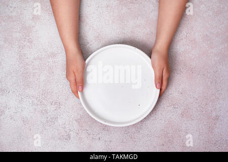 female hands hold an empty ceramic plate (tray). view from above. copy space - Stock Image