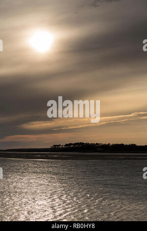 Sun behind clouds over the North Wales coast at Caernarfon - Stock Image