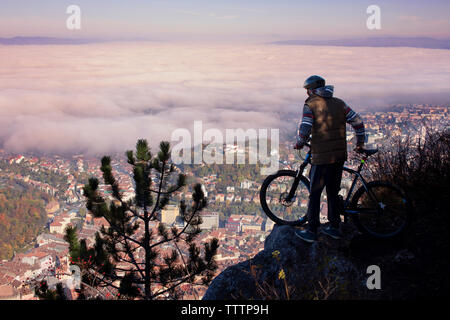 Rear view of cyclist looking at cityscape while standing on cliff - Stock Image