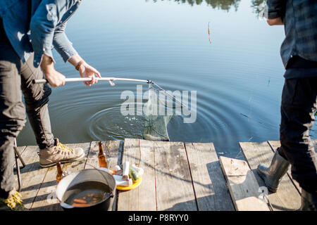 Fishermen catching big fish with fishing net on the lake in the morning - Stock Image