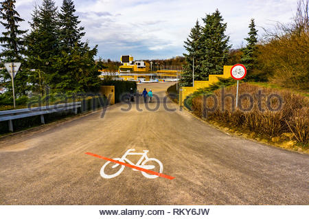 Poznan, Poland - February 10, 2019: Bicycle symbol with red line on a path with sign warning that bikes are not allowed at the Malta park on a cloudy  - Stock Image