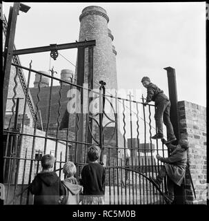 Westwood Mills, Lichfield Street, Hanley, Stoke-on-Trent, Staffordshire, 1965-1968. A group of children climbing the wrought iron gates at the canal side entrance to George Goodwin and Sons' Westwood Mills. - Stock Image