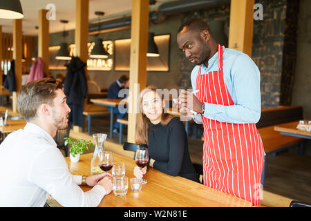 African man as a waiter takes the guests order in the restaurant - Stock Image