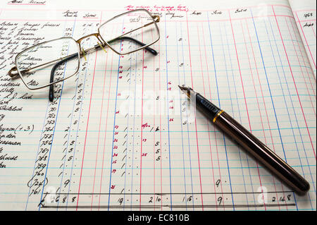 An old accounts ledger, figures in pounds shillings and pence, with fountain pen and glasses - Stock Image