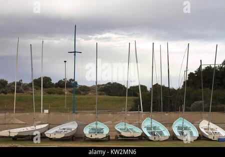 Sven small sailboats lined up in a boatyard, facing inland with grey cloudy sky. - Stock Image