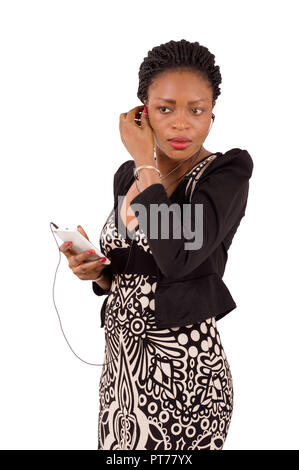 Young woman attentive phone with headphones standing on a white background. - Stock Image