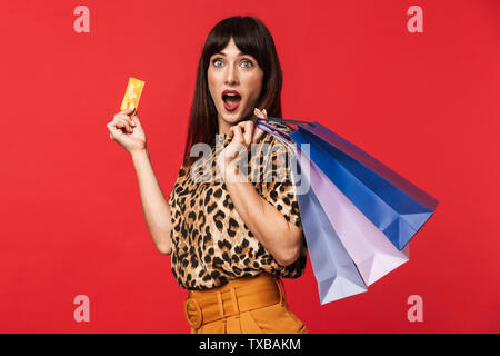 Image of a beautiful shocked young woman dressed in animal printed shirt posing isolated over red background holding credit card and shopping bags. - Stock Image