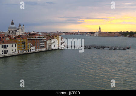 Pontoons and waterfront buildings on the bank of the Canale della Guidecca in early morning light, Venice, Italy - Stock Image