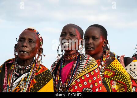 Three Masai women, missing teeth, one old, singing in a village near the Masai Mara, Kenya, East Africa. - Stock Image