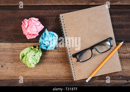 Colorful crumpled paper, eyeglasses, pencil and a spiral notebook on a wooden table. Concept of school, college, study, writer and diary - Stock Image