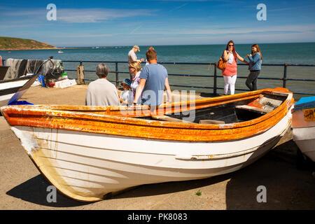 UK, England, Yorkshire, Filey, Coble Landing, visitors resting on boats in sunshine - Stock Image
