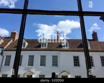 Georgian houses in Warwick, UK, under a blue sky seen through a sash window - Stock Image