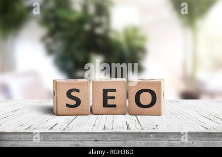 SEO word sign on a table in a bright room with green plants - Stock Image