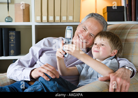 Boy and grandfather with camera phone - Stock Image